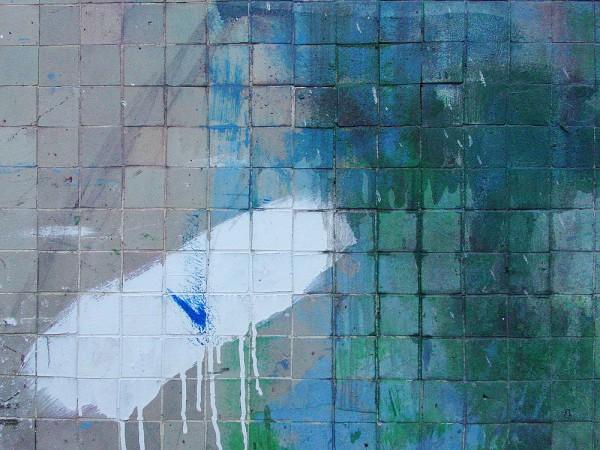 Limpiando la brocha en la pared después de pintar una barca